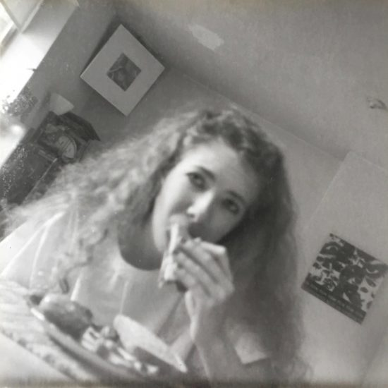 girl with curly hair eating sandwich