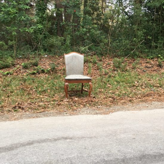 empty upholstered dining room chair on a roadside
