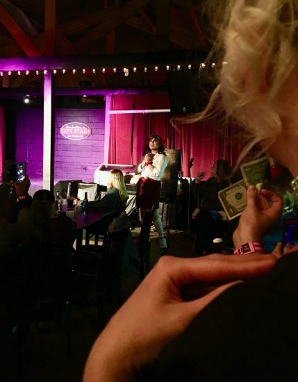 person holding dollar bill to tip entertainer