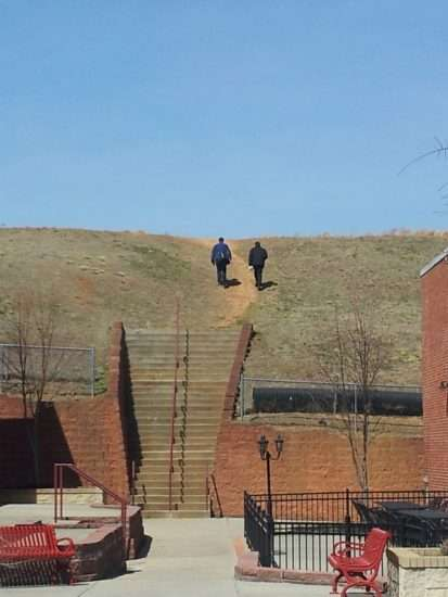 two people walking up a hill in the distance