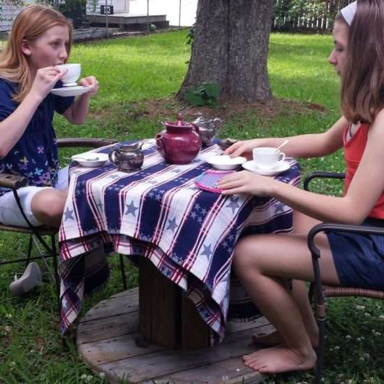 two young girls having a tea party outdoors on tablecloth with stars and stripes