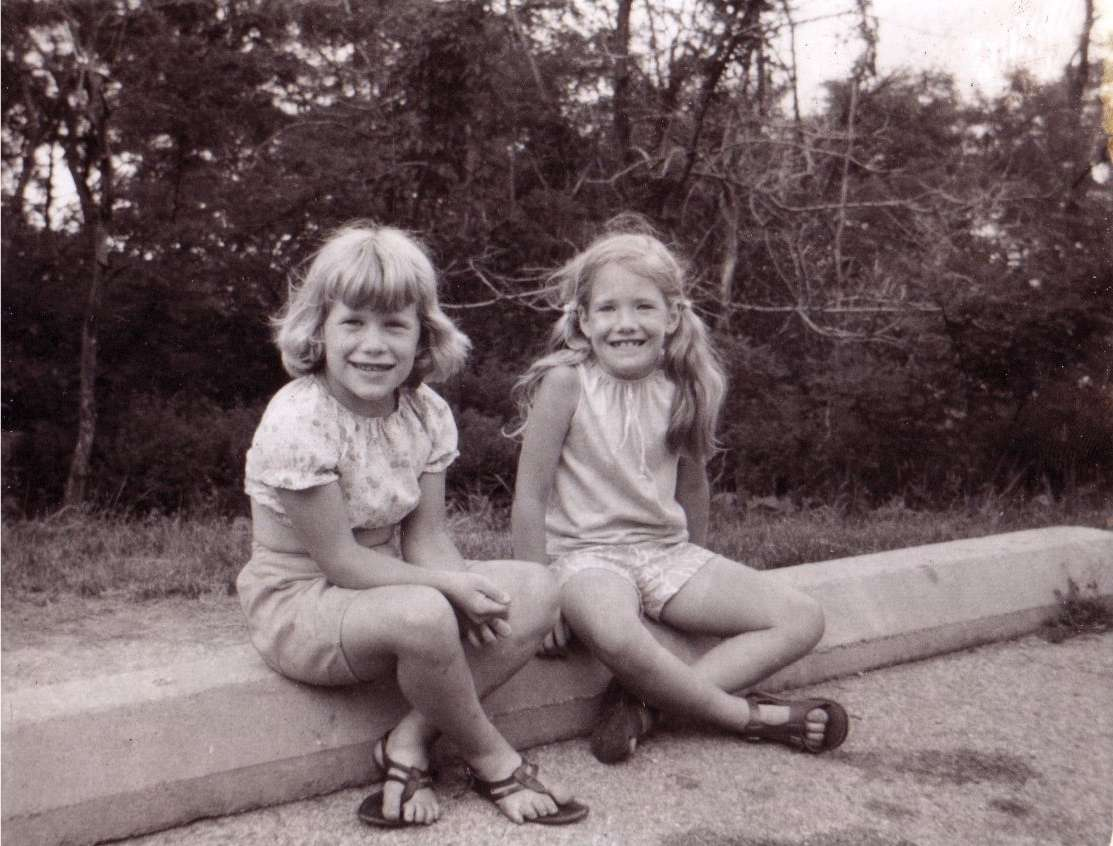 two little girls sitting on a curb in the early 1970s