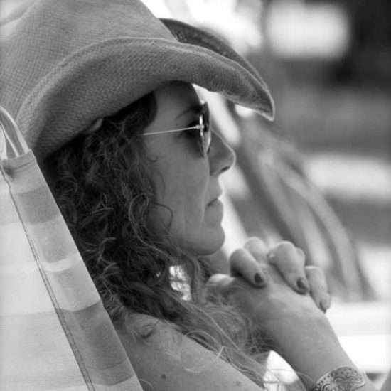 black and white photo of girl in profile wearing sunglasses and cowboy hat