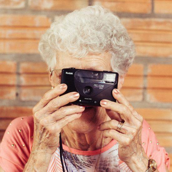 older woman holding camera