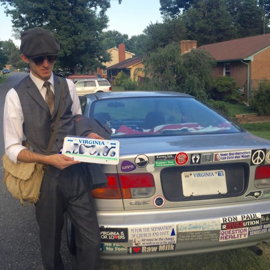 young man wearing newsboy cap, vest, and tie, standing behind honda civic with many bumper stickers