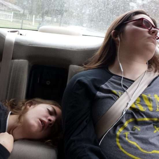 two girls asleep in the back seat of a car, one with a nirvana t-shirt and earbuds, one with her mouth open