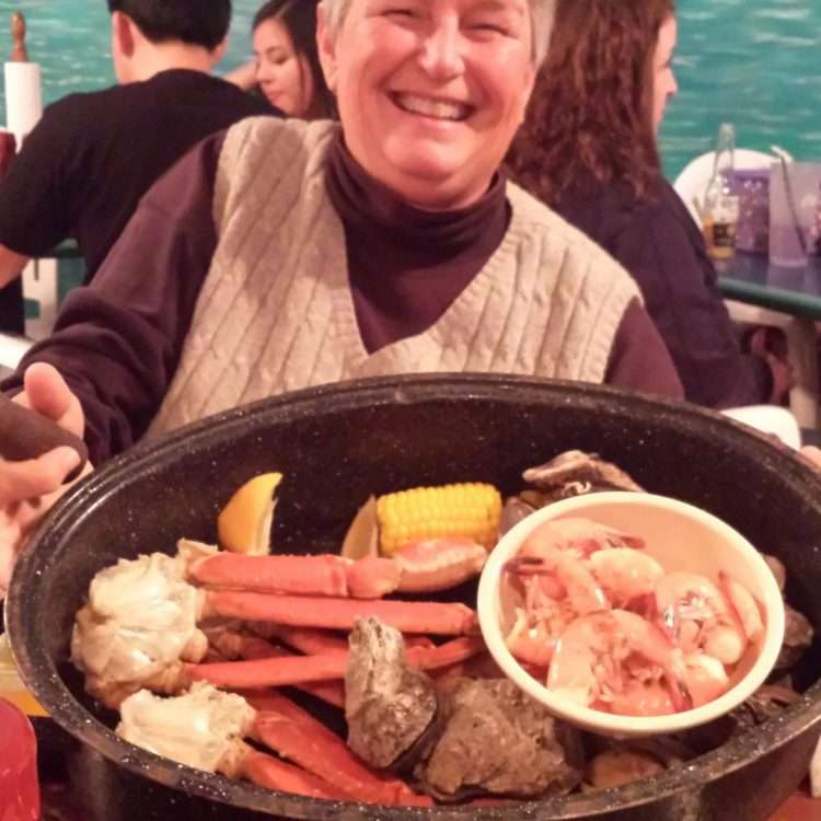 smiling woman holding a platter of low country boil- shrimp, potatoes, crab legs, corn