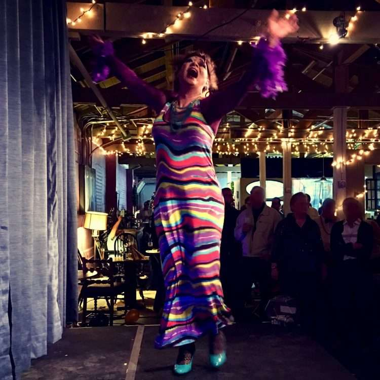 drag queen in striped dress throwing her hands into the air and singing