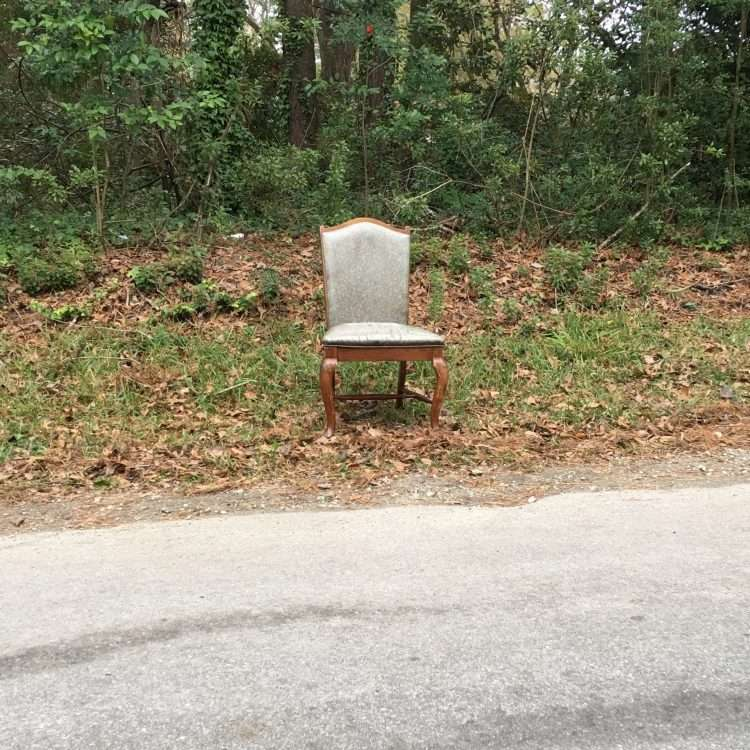 empty upholstered chair on a roadside
