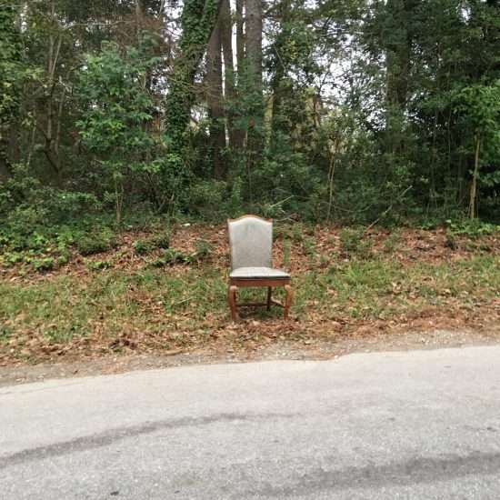 empty upholstered chair sitting on roadside