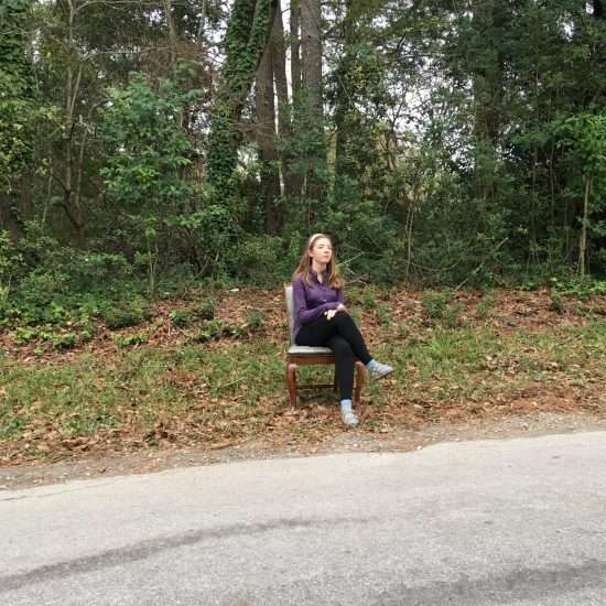 girl in chair on side of road