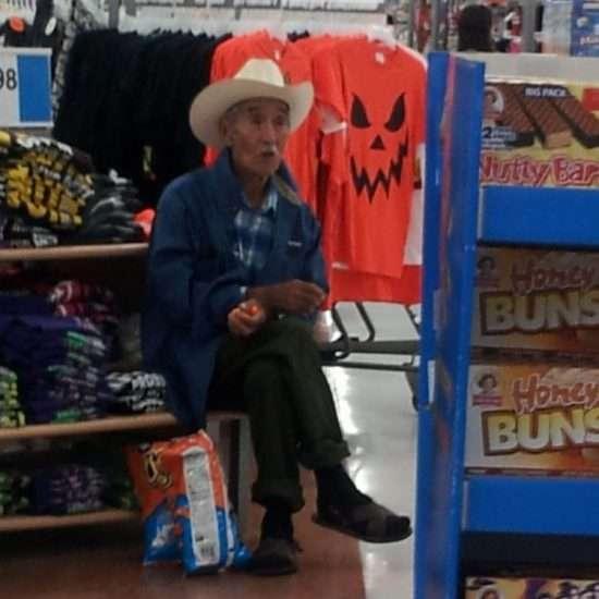man in cowboy hat, eating cheetos in walmart