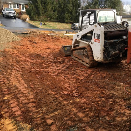 small bulldozer or ditch wizard digging red clay earth in front yard