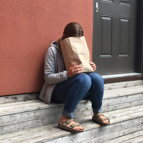 brunette girl sitting on wooden steps looking into or hiding her face in a brown paper bag