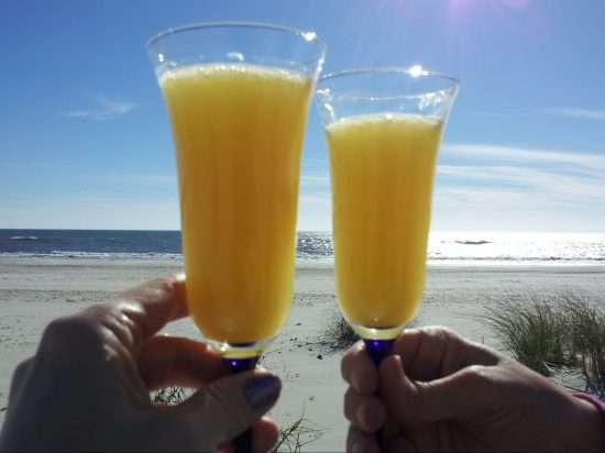 two champagne glasses raised to make a toast at the beach