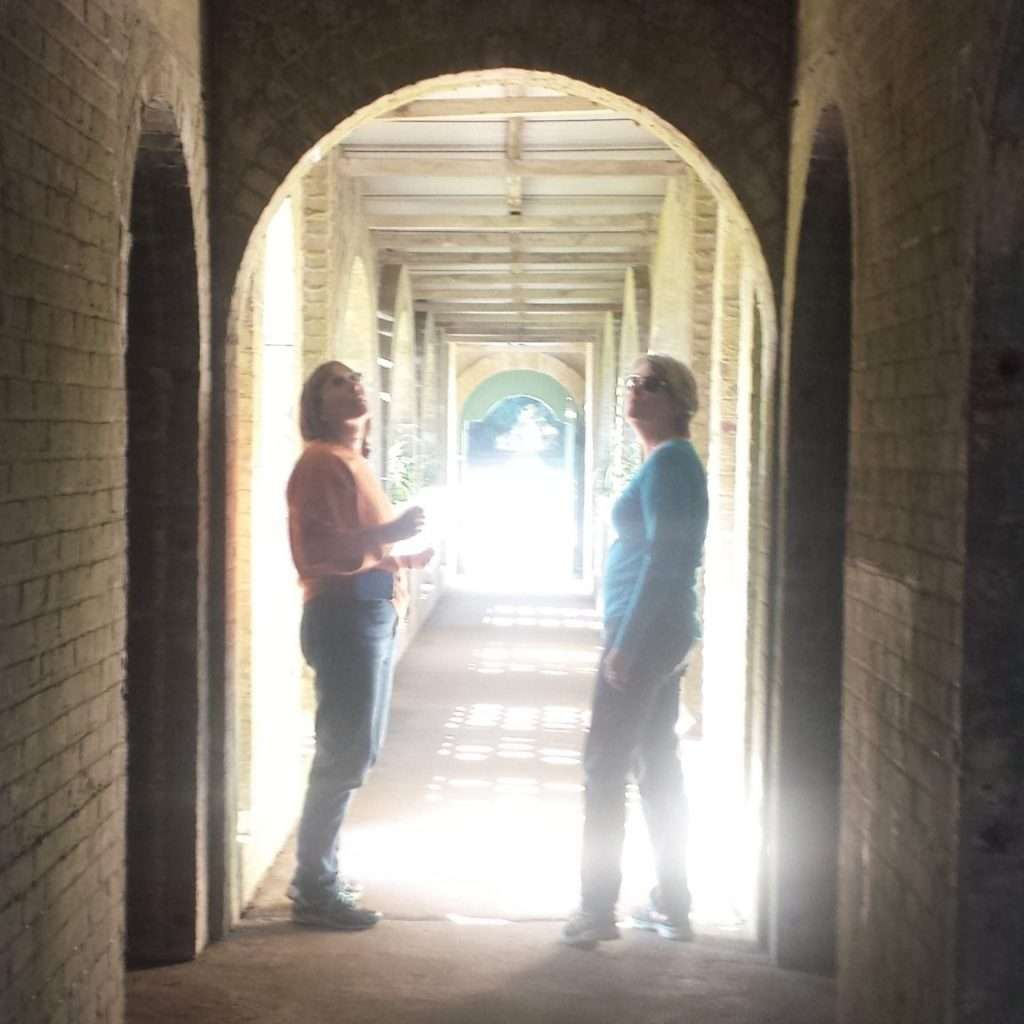 two women standing in a lighted tunnel