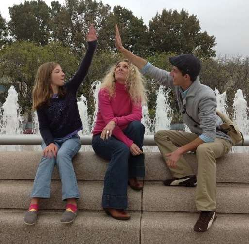 three people in front of a water fountain