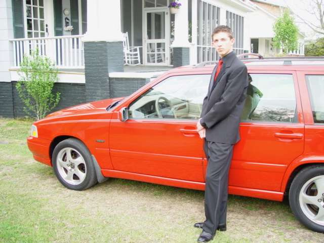 teenaged boy wearing black tux and red tie standing in front of red volvo v70