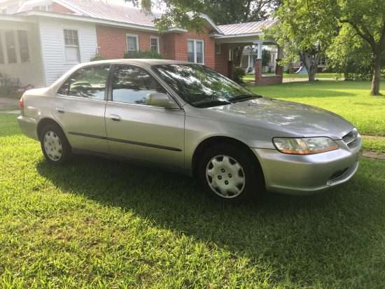 1998 silver honda civic parked in yard beside a brick house