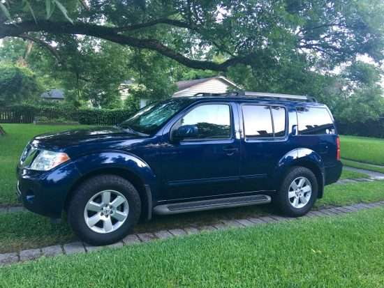 shiny dark blue 1998 nissan pathfinder parked on grass