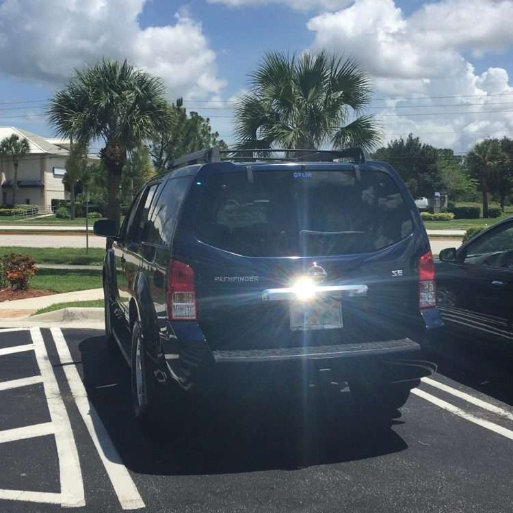 dark blue nissan pathfinder parked in florida with palm trees and blue skies