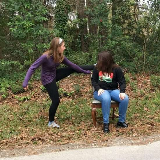 two young girls goofing off outdoors