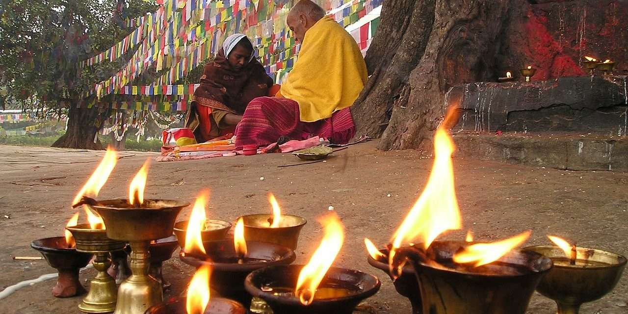 tibetan monks with prayer flags and candles