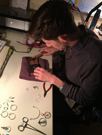 overhead view of young man making something at desk