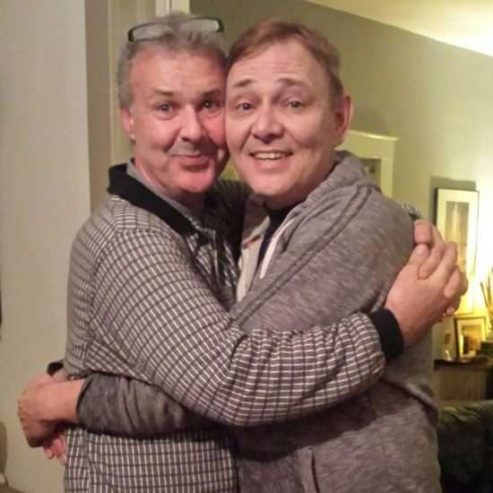2 happy guys hugging