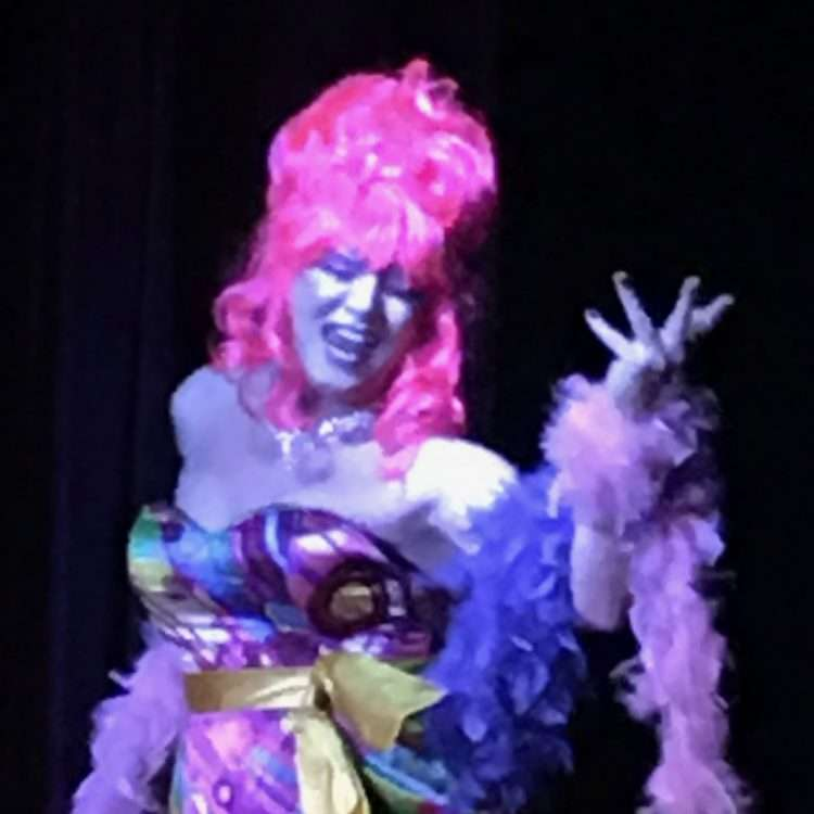 Drag queen with tall pink wig, singing with expression