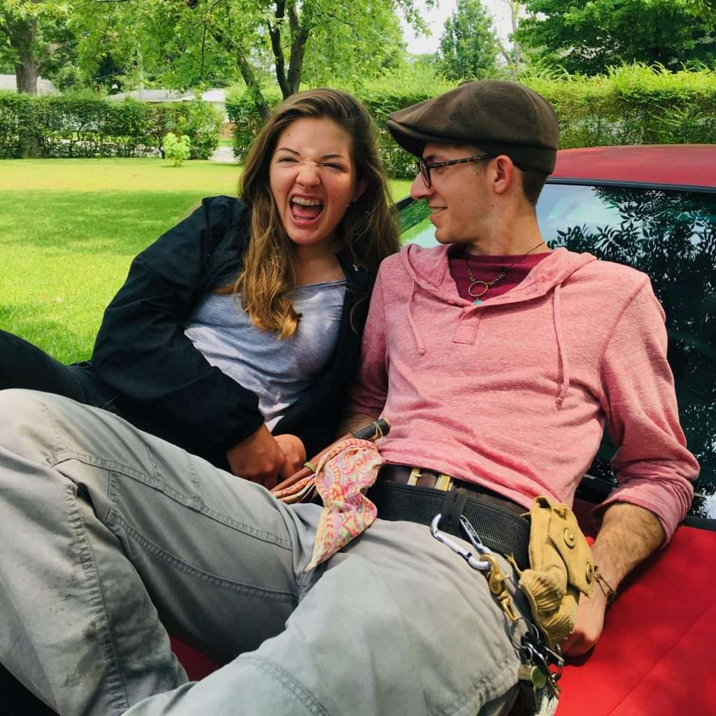 two young adults sitting on a car hood laughing and smiling