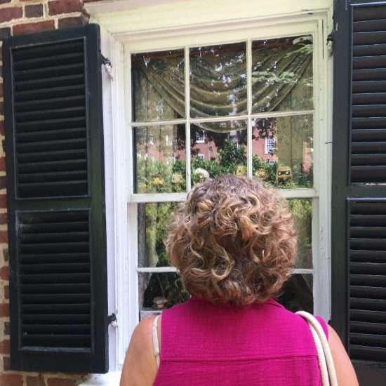 woman with curly hair looking at white double-hung window with black shutters