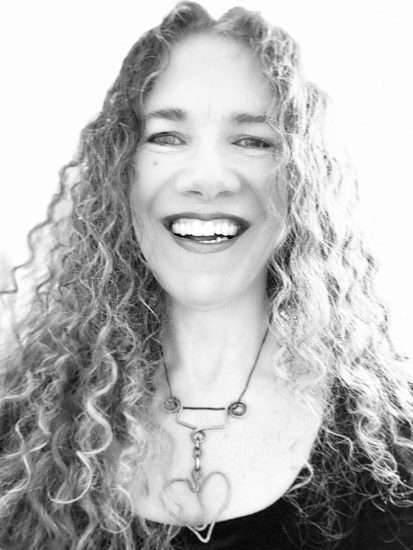 woman with curly hair, smiling at camera